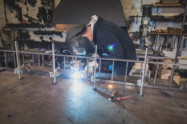 A blacksmith wears safety gear and is welding a metal construction in a metalsmith's workshop