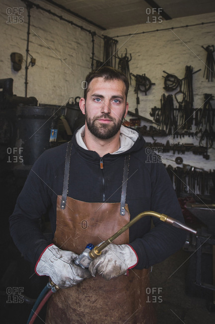 A blacksmith in a leather apron and with a cutting torch is portrayed in his workshop