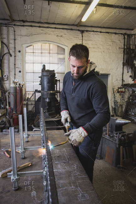A blacksmith is using a cutting torch in his workshop