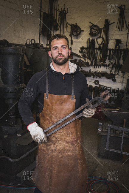 A blacksmith in a leather apron carries a tong and is portrayed in his workshop