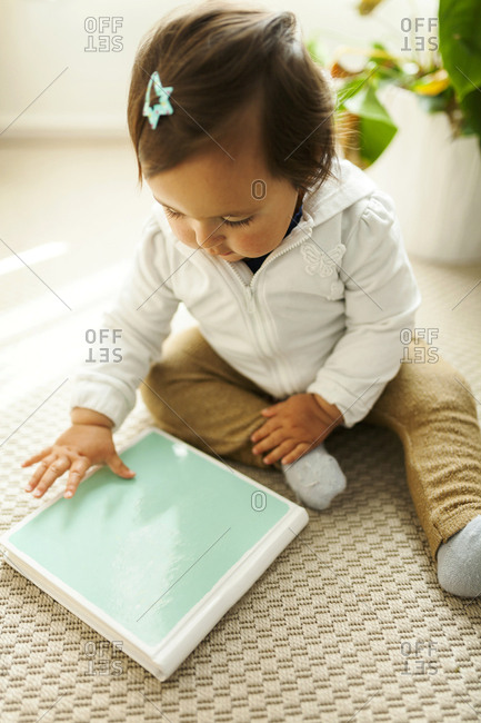 Baby sitting on floor touching book