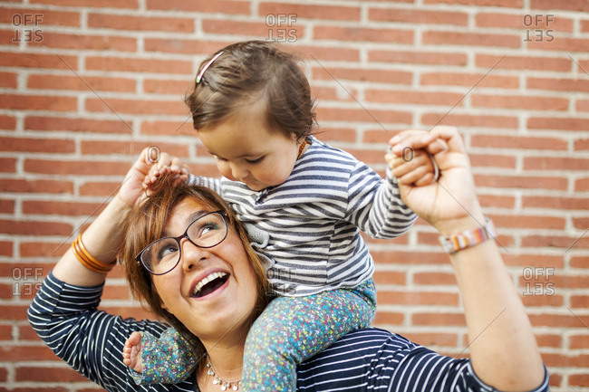 Smiling mother carrying baby on shoulders
