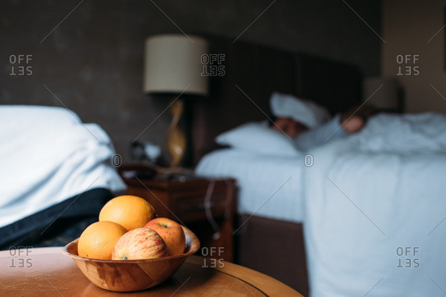 Wood bowl of fruit in foreground with man asleep in background