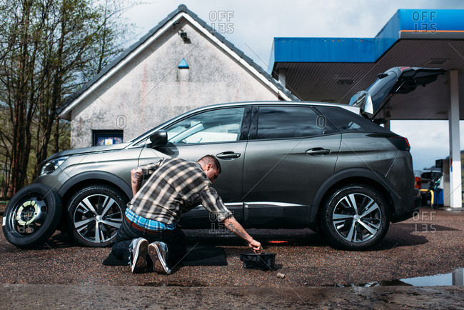 Man fixing a flat tire, Scotland