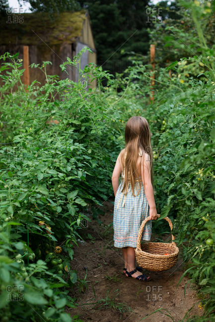 Young girl carrying basket in garden