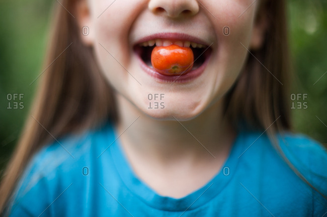 Young girl biting a small tomato