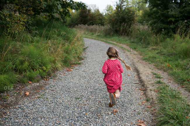 Rear view of girl running on gravel path