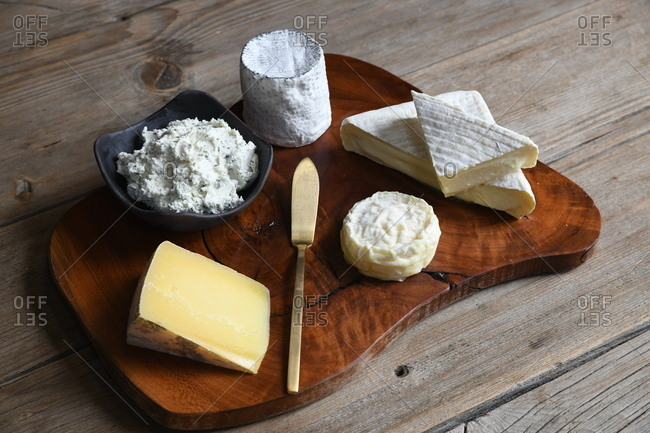 Top view of a variety of cheese on a wooden board