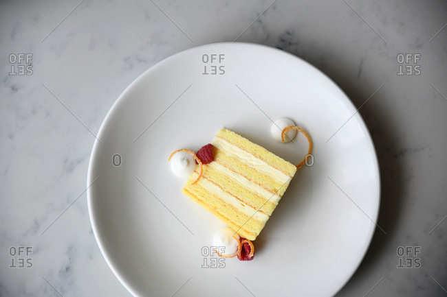 Slice of four-layer cake and raspberries