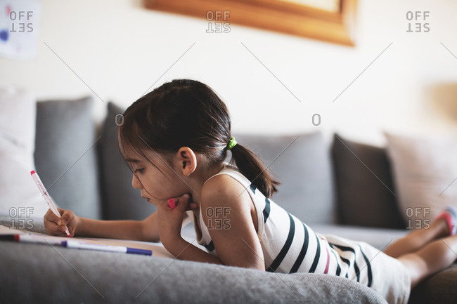 Girl on sofa drawing picture