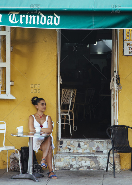 Cartagena de Indias, Colombia - February 9, 2018: Woman sitting at a cafe in Getsemani, Cartagena de Indias, Colombia