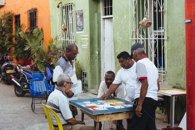 Cartagena de Indias, Colombia - February 9, 2018: People playing board game in Getsemani, Cartagena de Indias, Colombia