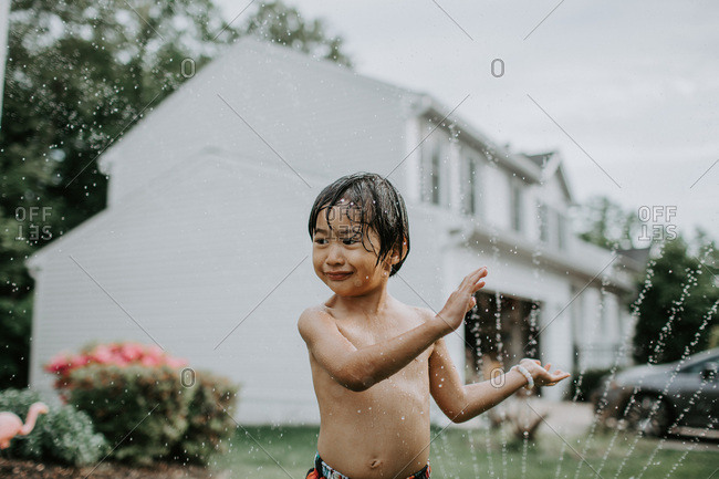 Boy cooling off with sprinkler in the yard