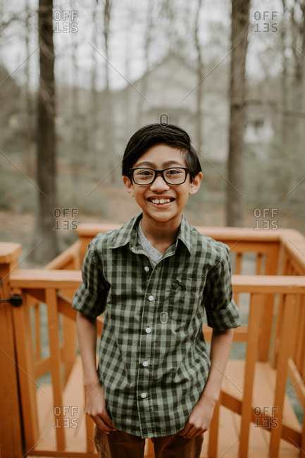 Closeup of brunette boy with glasses smiling on patio deck