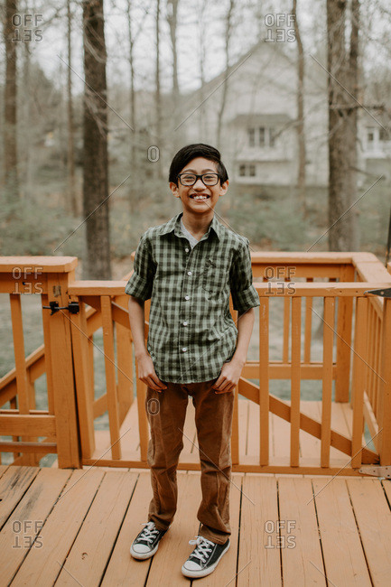 Middle school boy with glasses smiling on backyard deck