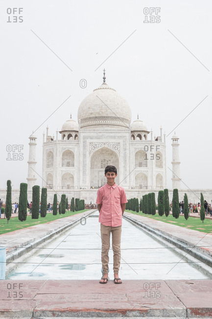 Teenage tourist posed in front of Taj Mahal