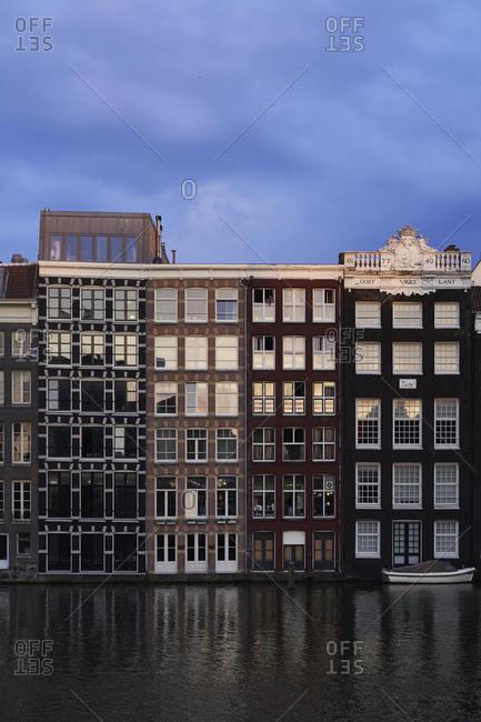 Amsterdam, Netherlands - May 22, 2018: Sunset lit residential canal neighborhood