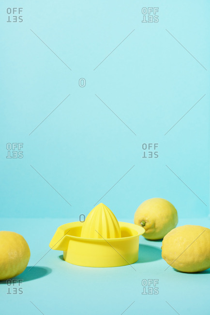 Full lemons around juicer in colorful solid background