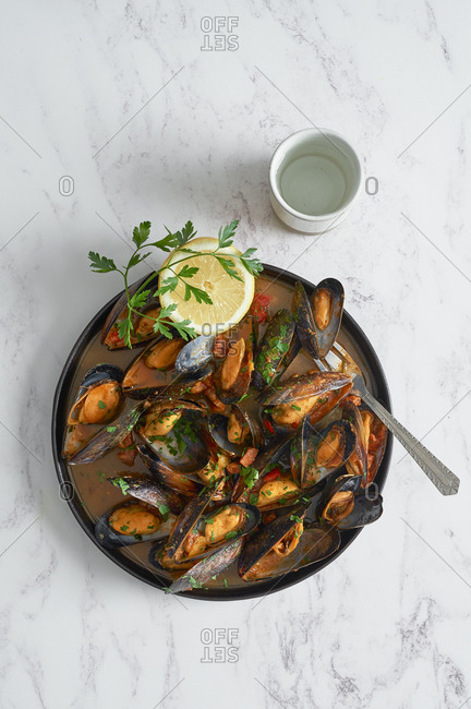 Top view fresh mussel platter with chorizo and tomato sauce served on marble countertop
