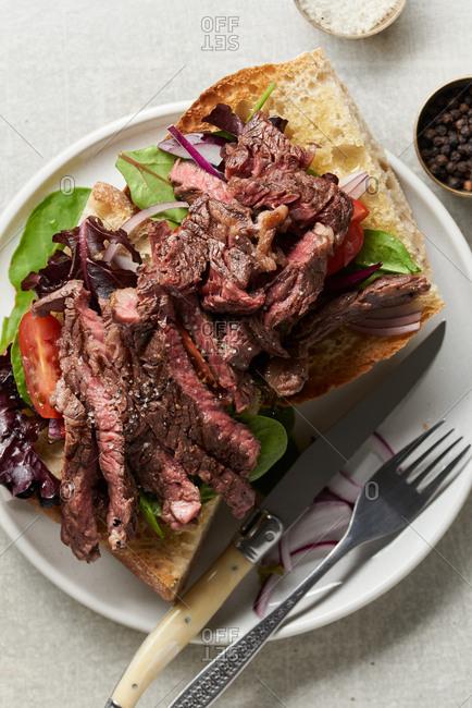 Open-faced steak sandwich on a restaurant plate