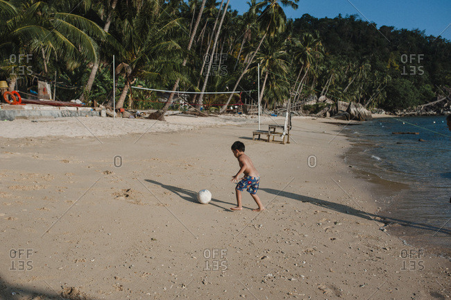 Young boy running after ball on Malaysian beach