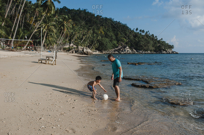 Father and son playing with ball on exotic beach