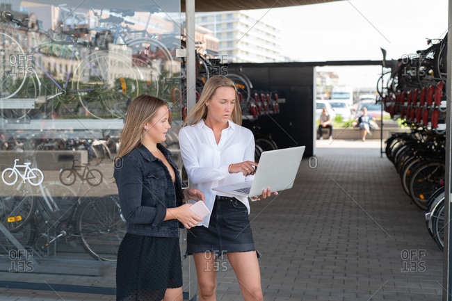 Two women viewing computer screen outside bike shop