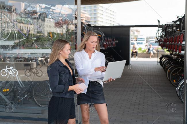Two women viewing computer screen outside bike shop