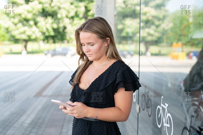 Woman looking at smartphone outside of bicycle storefront