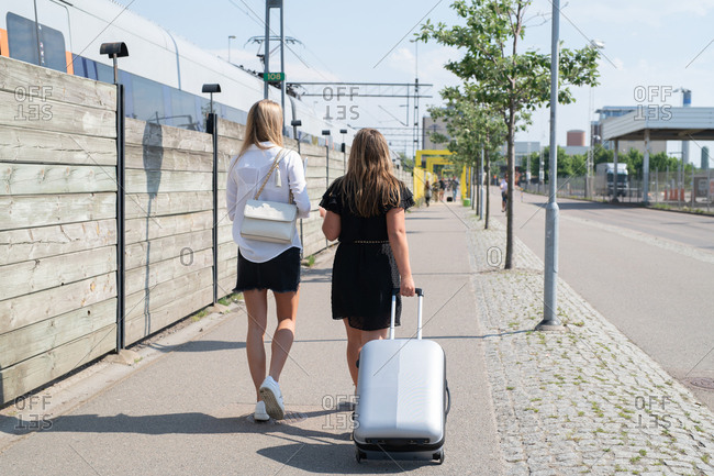 Female pedestrians outside train station on sunny day