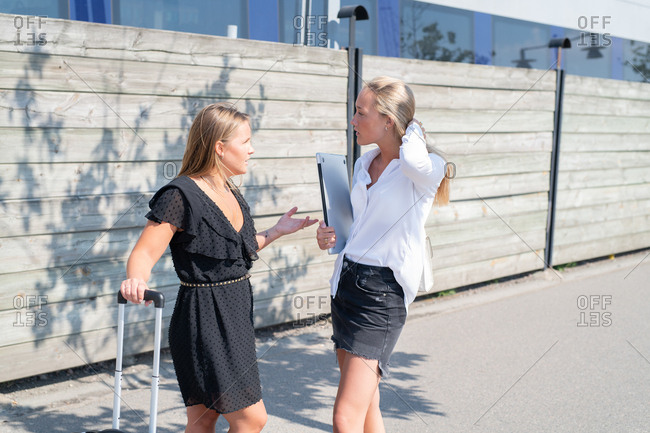 Businesswomen having conversation on sunny sidewalk