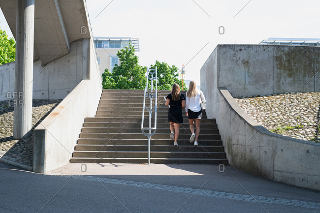Back view of two women walking up outdoor steps