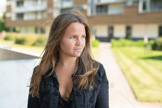Thoughtful woman in dark denim jacket standing outside