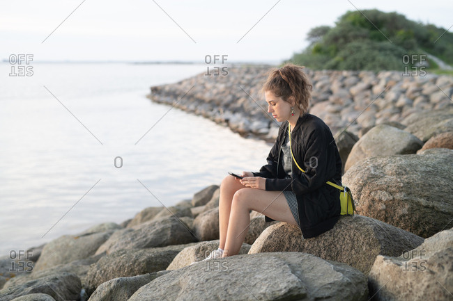 Young woman sitting alone on rocky lake shore looking at cell phone