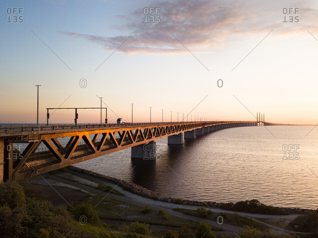 Park view of sunset on long bridge over water
