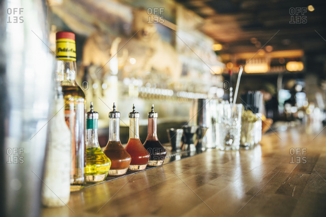 Angled view of wooden bar top with bottled condiments