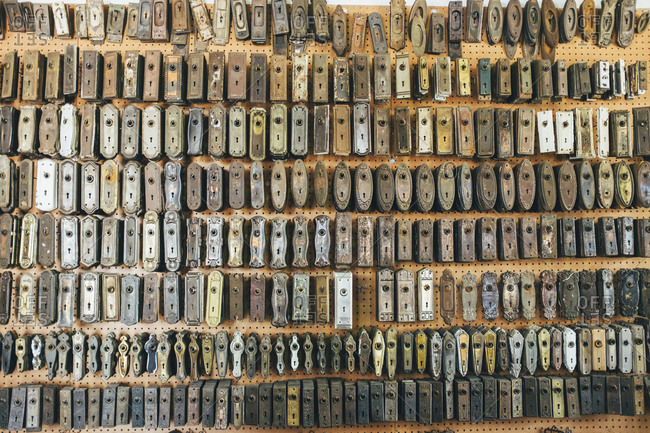 Assorted vintage door lock components hanging on store wall