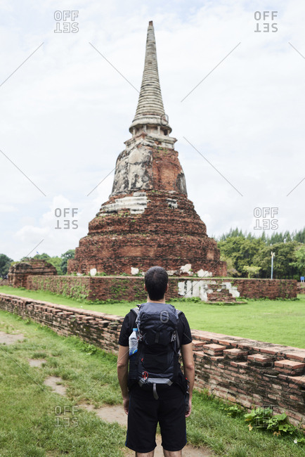 Backpacker contemplating an ancient building in Ayutthaya ruins, Thailand