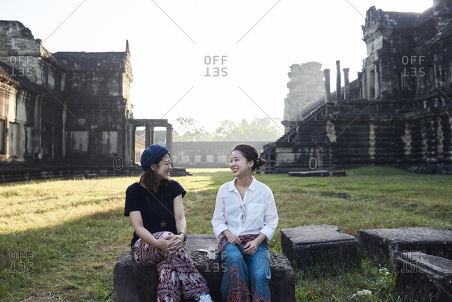 Japanese best friends chatting and sitting on stone against Angkor Wat temple in background early morning light