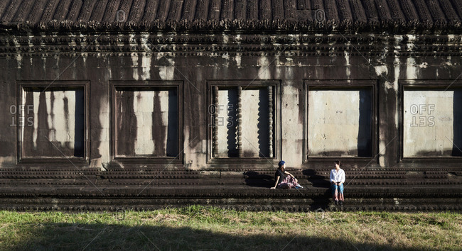 Japanese friends chatting and sitting on stone bench against Angkor Wat temple in background in sunlight