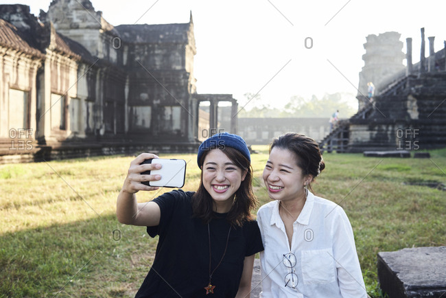 Asian friends posing for a self-portrait taken with smartphone against Angkor Wat temple in early morning light