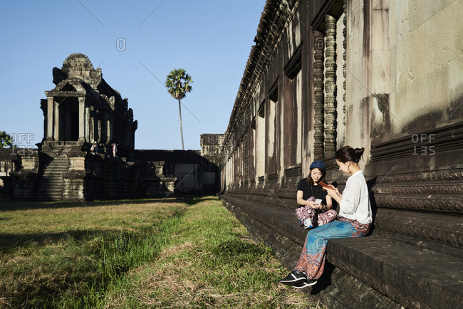 Friends using smartphone while sitting on stone bench with Angkor Wat temple in background at sunlight