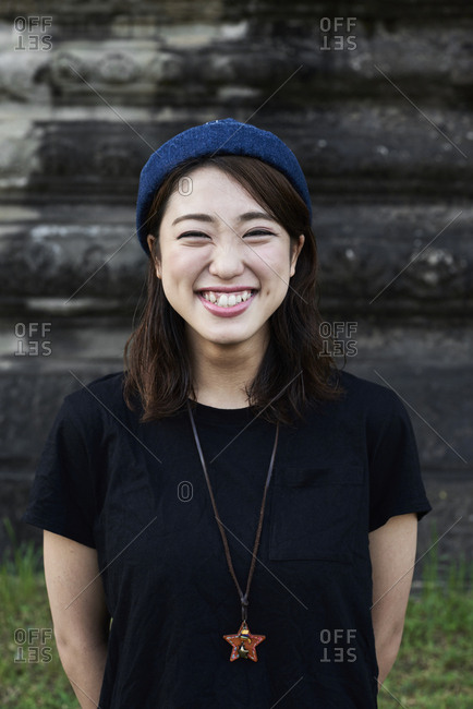 Portrait of a happy Japanese female traveler in Angkor Wat, Cambodia
