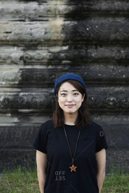 Portrait of a Japanese female traveler wearing blue hat and star necklace in Angkor Wat, Cambodia