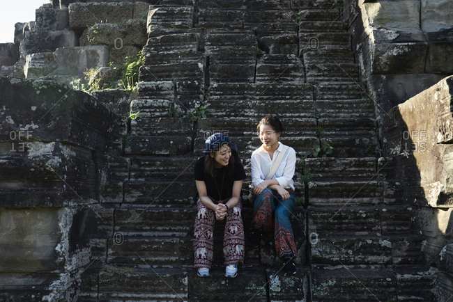 Friends sitting on an ancient stone staircase having fun together