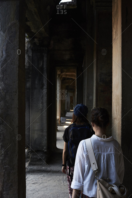 Japanese female travelers walking across corridor inside temple of Angkor Wat, Cambodia