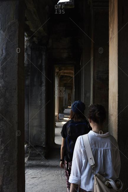 Japanese female travelers walking across corridor inside temple of Angkor Wat, Cambodia