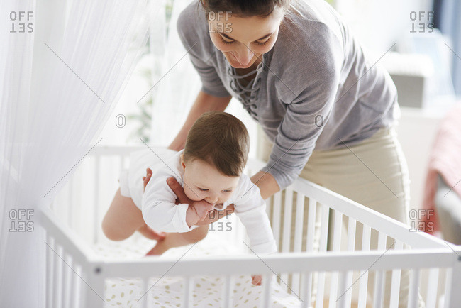 Mother laying her baby into crib at home