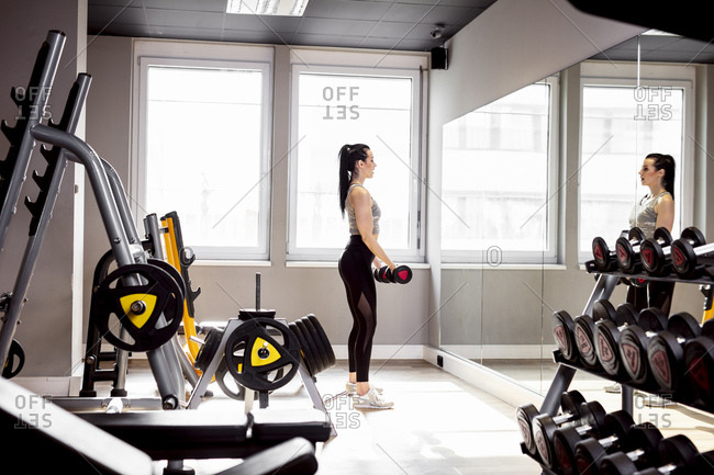 Woman lifting dumbbells in gym looking in mirror