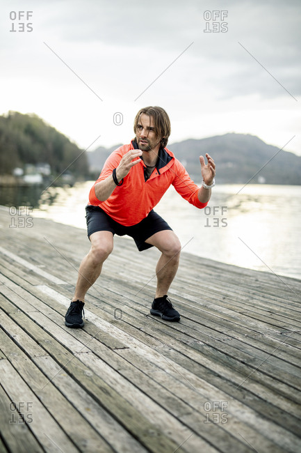 Athlete exercising on wooden deck at the lakeshore